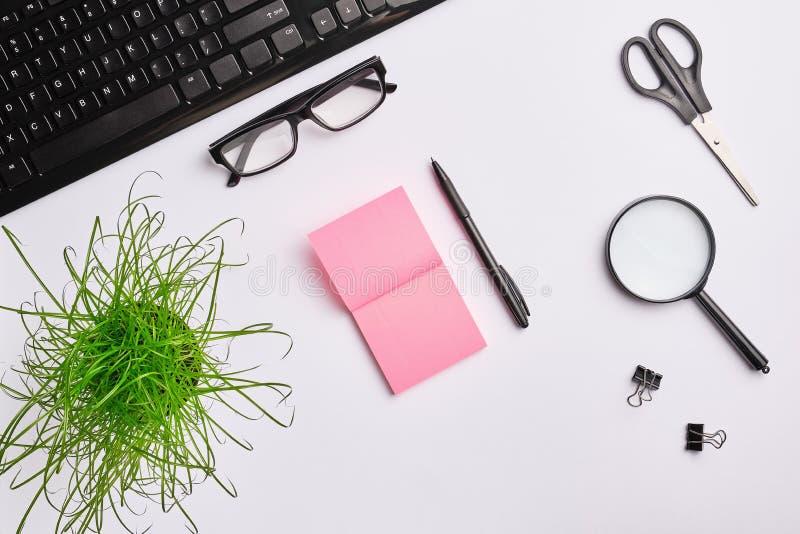 Weiße Tabelle mit Tastatur, Lupe, Aufklebern, Scheren, Büroanlage, Clipn und Stift lizenzfreies stockbild