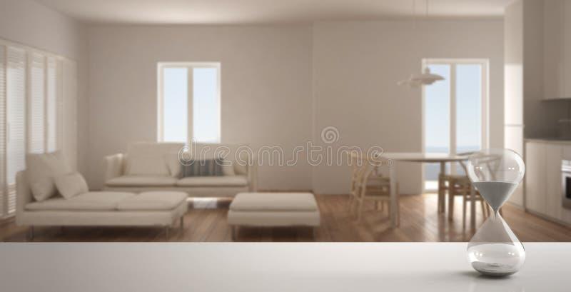 Weiße Tabelle oder Regal mit der Kristallsanduhr, welche die Verstreichungszeit über unscharfem leerem Raum, Wohnzimmer mit Küche lizenzfreie abbildung