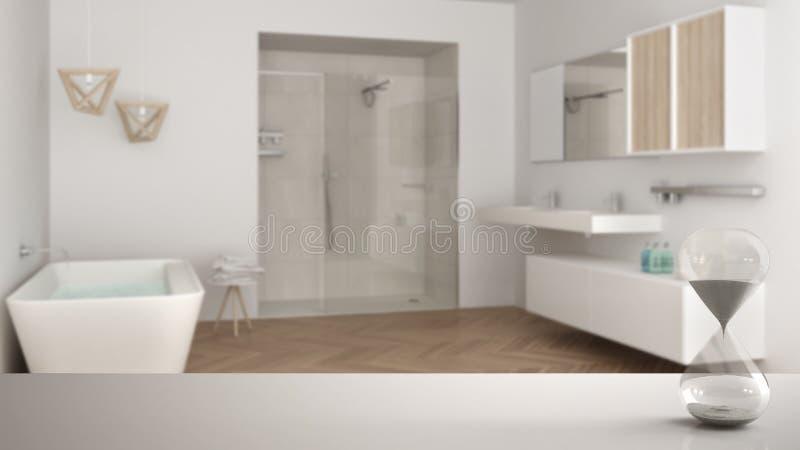 Weiße Tabelle oder Regal mit der Kristallsanduhr, welche die Verstreichungszeit über unscharfem modernem Badezimmer mit Badewanne lizenzfreie stockfotografie