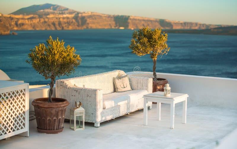 Weiße Tabelle und Sofas Dorf im Freien auf der Terrasse Unterlassungsmeer, Oia, Santorini, die Kykladen, Griechenland stockfoto