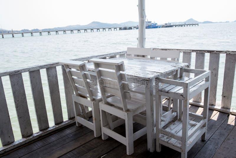 Weiße Tabellen und Stühle im Restaurant leerer Rattanmöbelkaffeesatz-Tabellenstuhl an der Bretterbodenseefront durch das Meer stockfotos