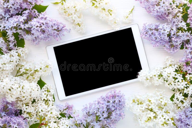 Weiße Tablet-Computer- und Fliederblumen auf weißem hölzernem backgrou stockfotos