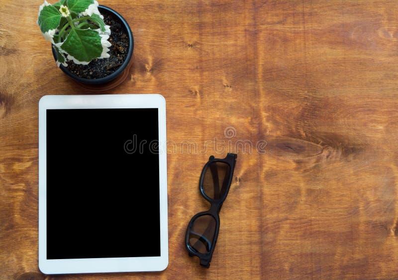 Weiße Tablette mit schwarzem leerem Bildschirm, frischer grüner Blume und schwarzen Gläsern auf hölzernem Hintergrund Copyspace-K lizenzfreies stockbild