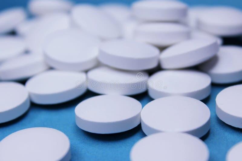 Weiße Tabletten der medizinischen Runde, Kalziumvitaminnahaufnahme auf blauem Hintergrund mit Raum für Text oder Bild Pillen stockbild