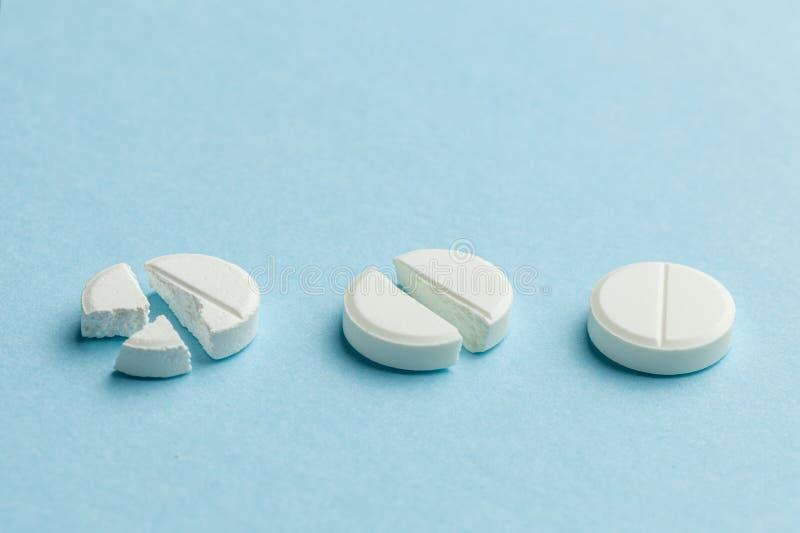 Weiße Tabletten mit blauem Hintergrund Nur wenige Tabletten zerbrochen in der Hälfte, wodurch die Dosis des Arzneimittels verring stockfotografie