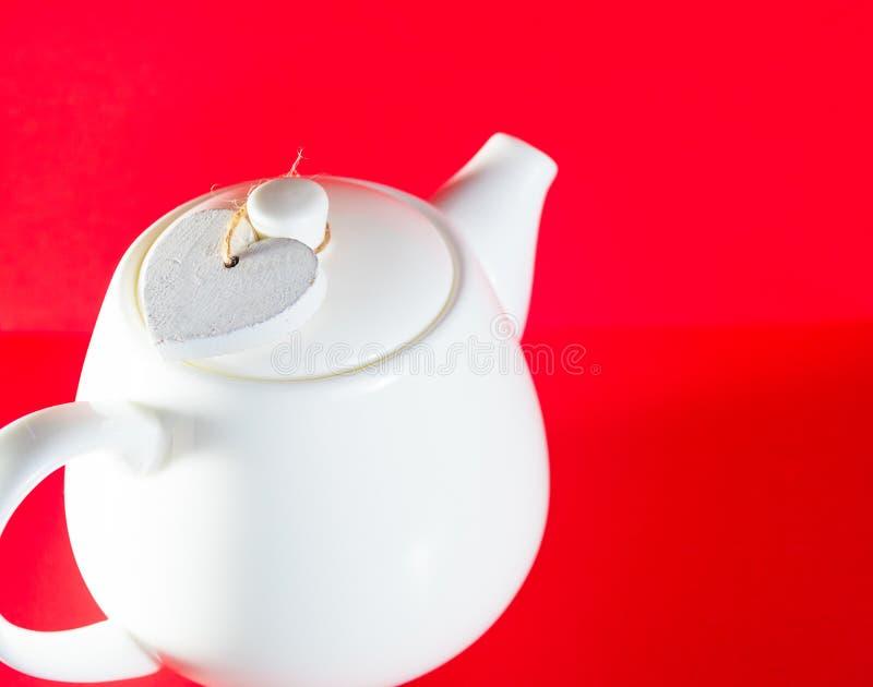 Weiße Teekanne weiße teekanne mit dem herzen gebunden mit einer schnur lokalisiert