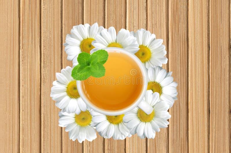 Weiße Teeschale mit Minze auf Kamille blüht auf hölzerner Beschaffenheit c lizenzfreies stockfoto