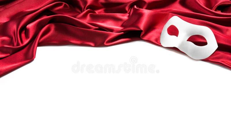 Weiße Theatermaske auf rotem Seidengewebe stockfoto