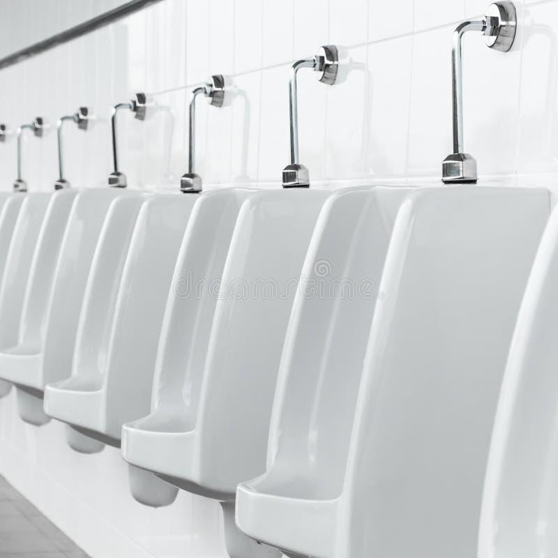 Weiße Toiletten in der Manntoilette lizenzfreies stockfoto