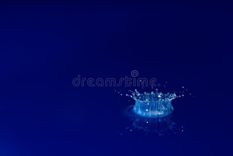 Weiße Tröpfchen, die in das Blau fallen stockbilder