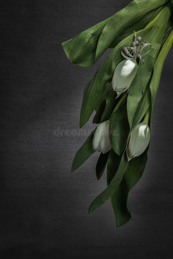 Weiße Tulpen auf Grey Background mit Ballerinaschmuck stockfoto