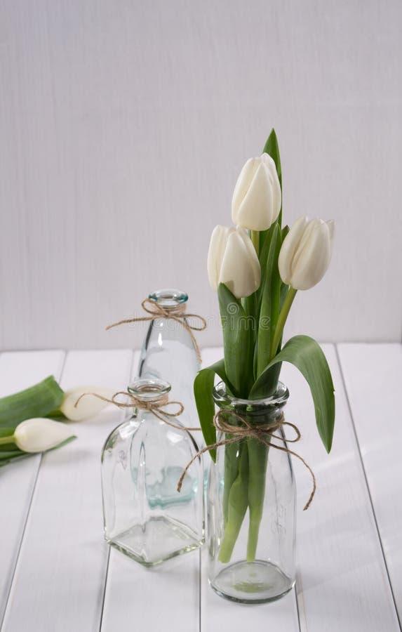 Weiße Tulpen in der Glasflasche lizenzfreie stockfotos