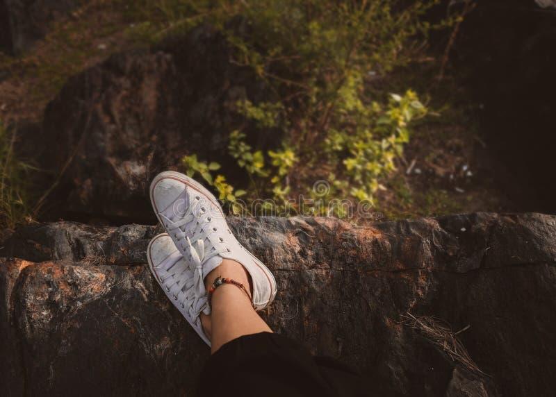 Weiße Turnschuhe auf den Beinen der Frau auf dem Felsen lizenzfreies stockbild