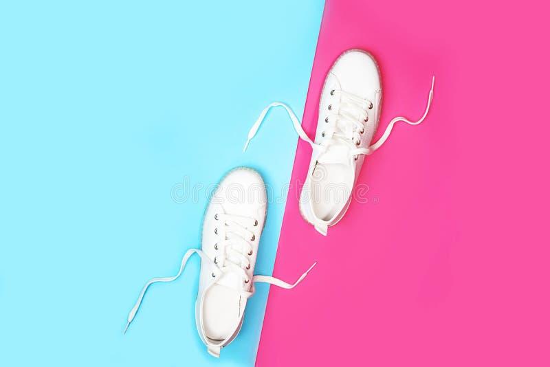 Weiße Turnschuhe liegen auf helle Neonfarbblauem rosa Hintergrund lizenzfreie stockfotografie