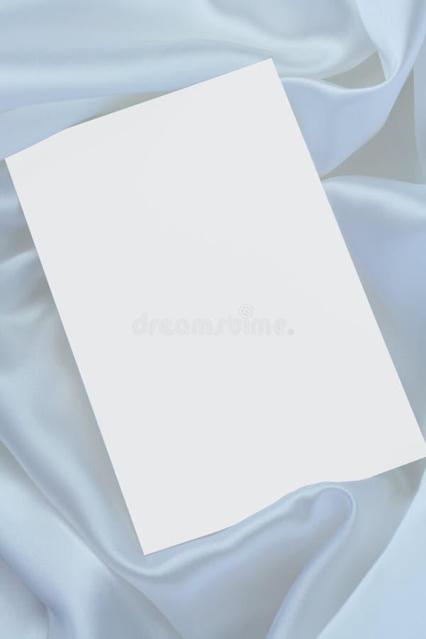 Weiße unbelegte Karte auf weißem Satin lizenzfreies stockbild