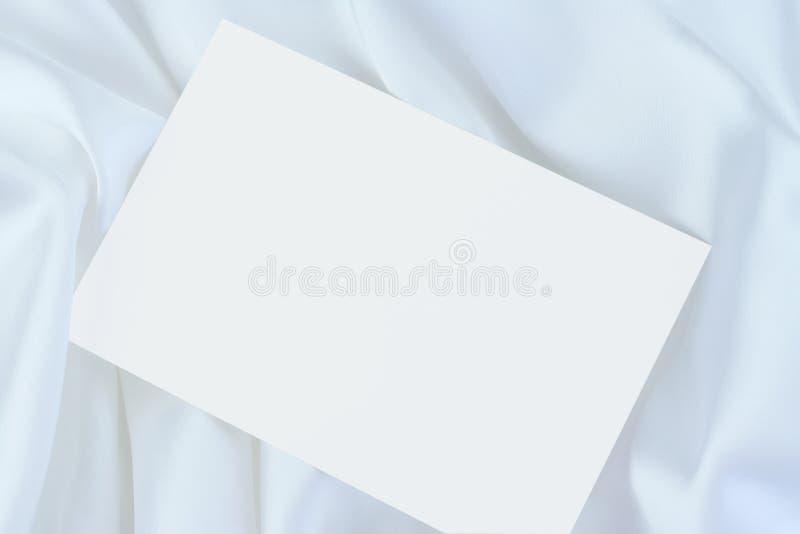 Weiße unbelegte Karte auf weißem Satin lizenzfreie stockfotografie
