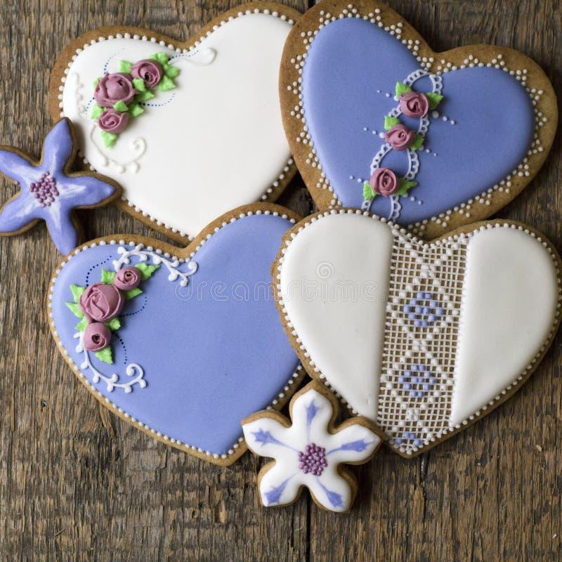 Weiße und lila Herz-förmige Plätzchen verziert mit Blumen und Stickerei in der Weinleseart auf hölzernem Hintergrund für Valentin stockfotos
