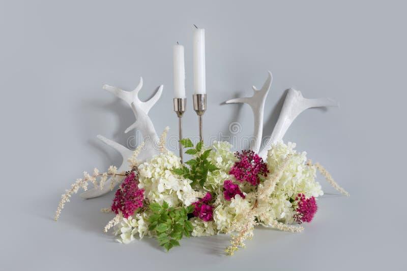 Weiße und purpurrote Wildflowers, Kerze und Rengeweihe auf Pastellgrau Element der Auslegung lizenzfreie stockbilder