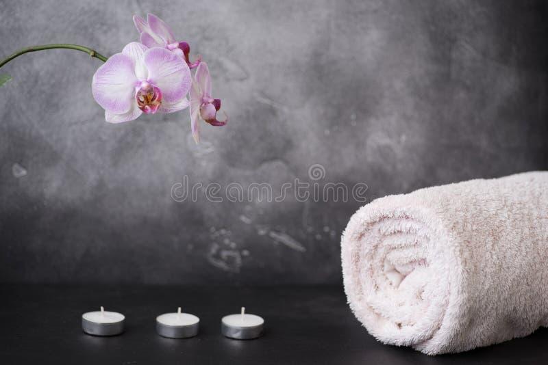 Weiße und rosa Mottenorchideenblumen, Tuch und drei Kerzen auf grauem Hintergrund lizenzfreie stockbilder
