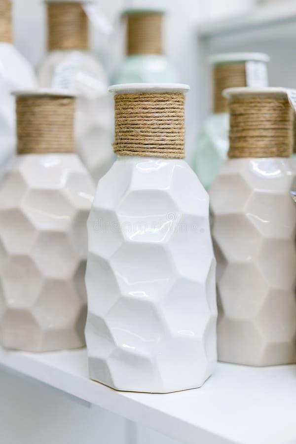 Weiße Vasen im Regal im Speicher Neue weiße Tongefäße im Blumengeschäft Vertikales Foto stockbild