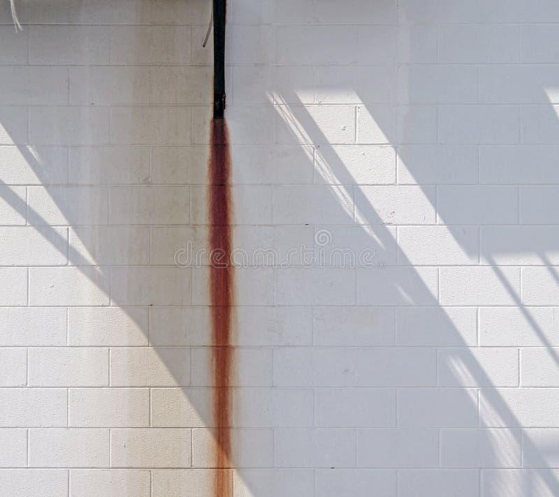 Weiße Wand mit Rost-Streifen und Schatten stockfotografie