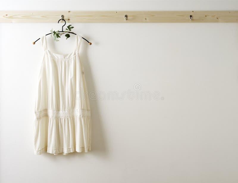 Weiße Wand und Kleidung auf einer Aufhängung. lizenzfreie stockbilder