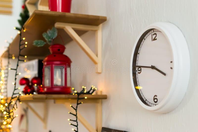 Weiße Wanduhr auf einem roten Kerzenständer des hölzernen Regals Metall Das neue Jahr ist 2019 Girlande und rote Weihnachtsbälle  stockfoto