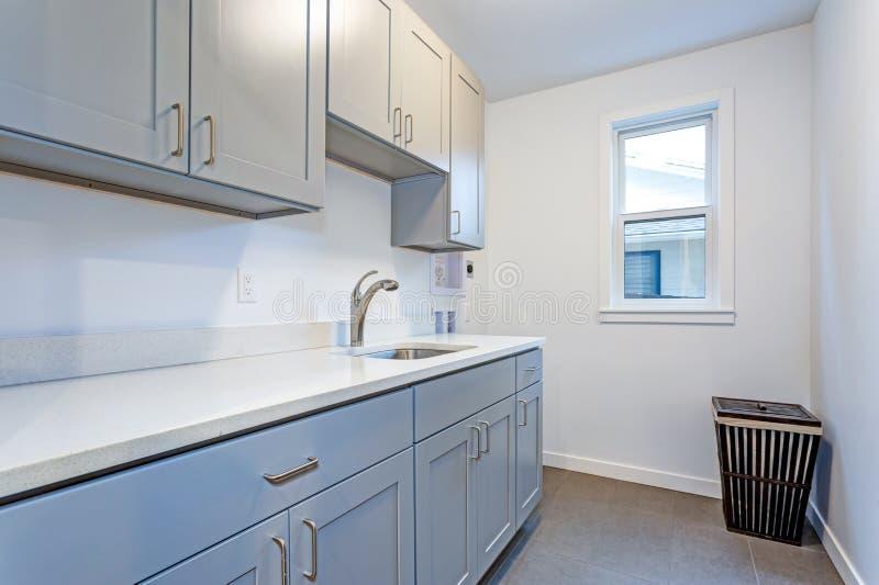 Weiße Waschküche mit blassen grauen Schüttel-Apparatkabinetten stockbild