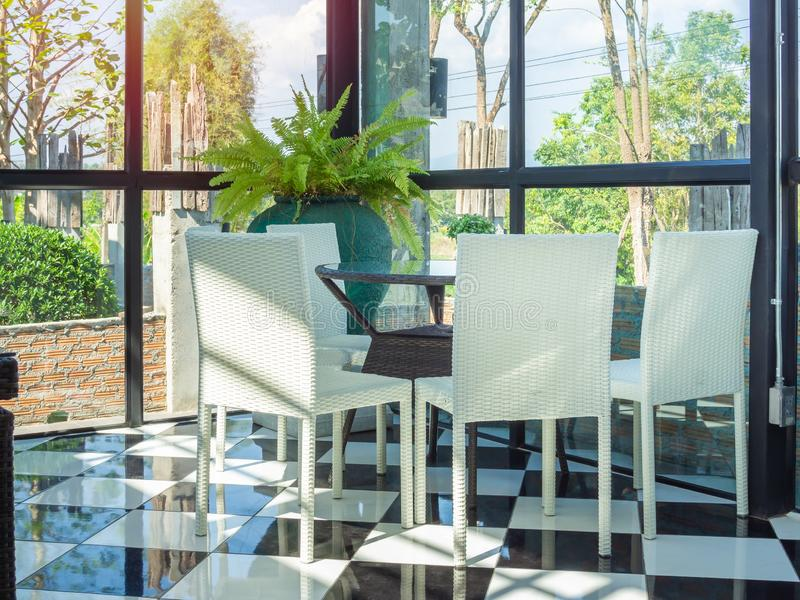 Weiße Webartstühle und braune Webarttabelle im Restaurant stockfotos