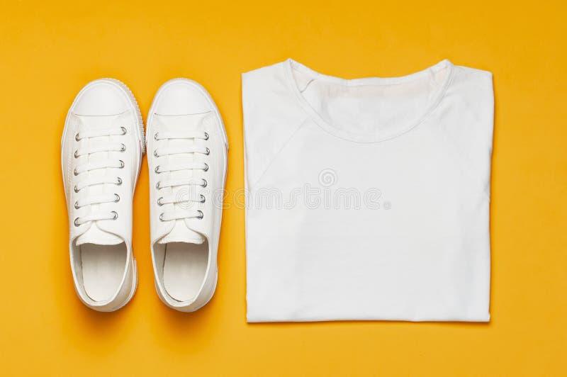 Weiße weibliche Modeturnschuhe, weißes T-Shirt auf gelb-orangeem Hintergrund Flacher Draufsicht-Kopienraum der Lage Frauen `s Sch lizenzfreie stockbilder