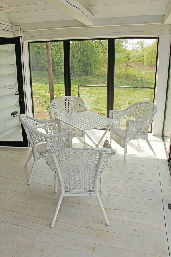 Weiße Weidenmöbel - Stühle, Stühle und Tabelle, in einem weißen ro lizenzfreie stockfotos