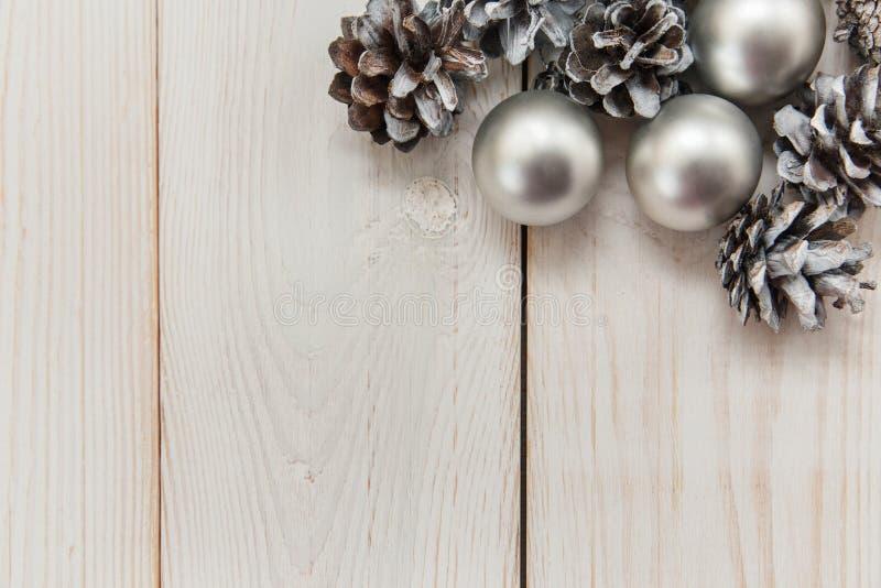Weiße Winterkegel auf dem Holztisch mit silbernen Bällen Abstraktes Hintergrundmuster der weißen Sterne auf dunkelroter Auslegung lizenzfreie stockfotografie