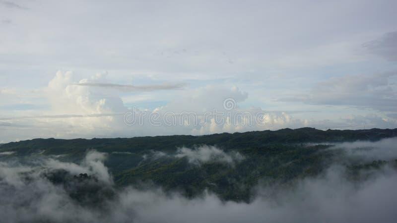 Weiße Wolken in den Bergen mit der Atmosphäre morgens stockbild