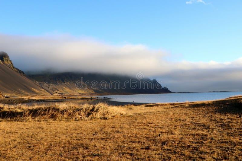 Weiße Wolken, die an den schwarzen Bergen nahe Hofn in Island hängen stockbilder