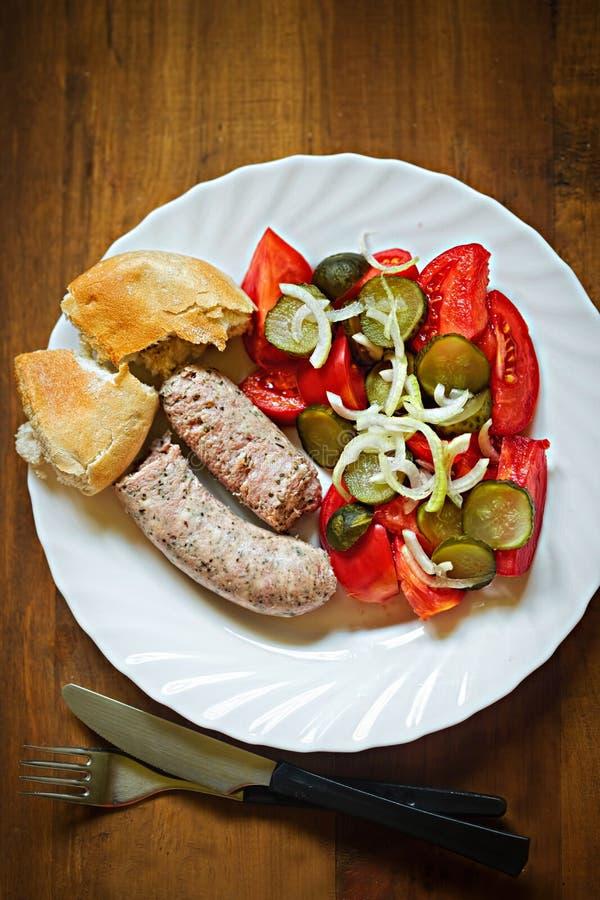 Weiße Wurst mit Essiggurke, Tomate, Zwiebelsalat und neuer Rolle lizenzfreies stockfoto