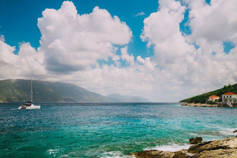 Weiße Yacht, die zur hohen See unter erstaunliches weißes endloses cloudscape geht Haarscharfes transparentes blaues Türkiswasser stockfotos