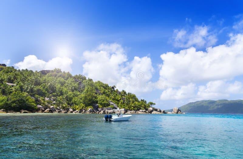 Weiße Yacht nahe sandiger Küste von Seychellen. lizenzfreies stockbild