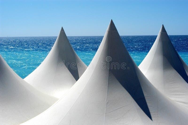 Weiße Zeltspitzen gegen Mittelmeer lizenzfreie stockfotos