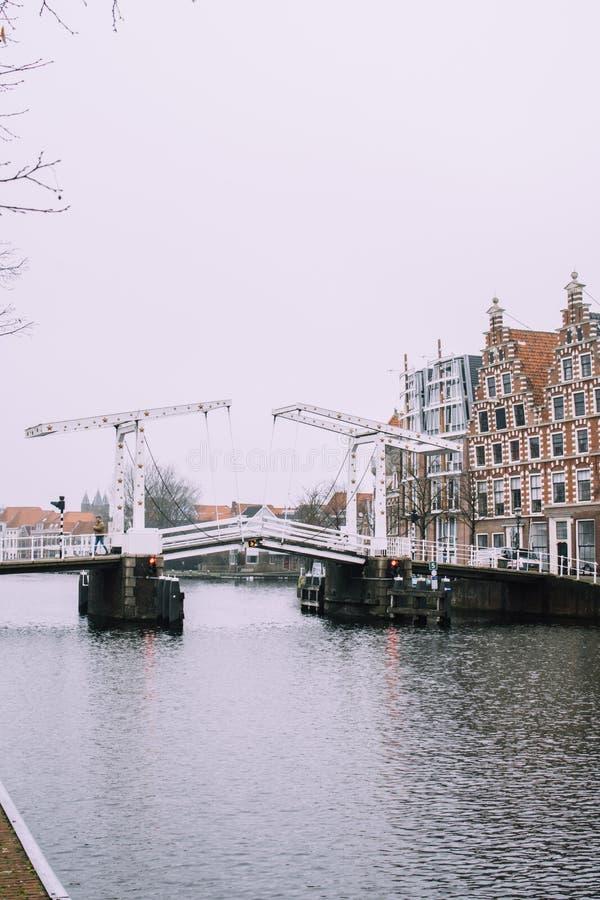 Weiße Zugbrücke über dem Wasser des Flusses in Haarlem, die Niederlande Typisches Holland-Stadtbild lizenzfreies stockfoto