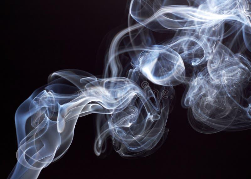 Weißer abstrakter Rauch von den aromatischen Stöcken auf einem schwarzen Hintergrund stockbild