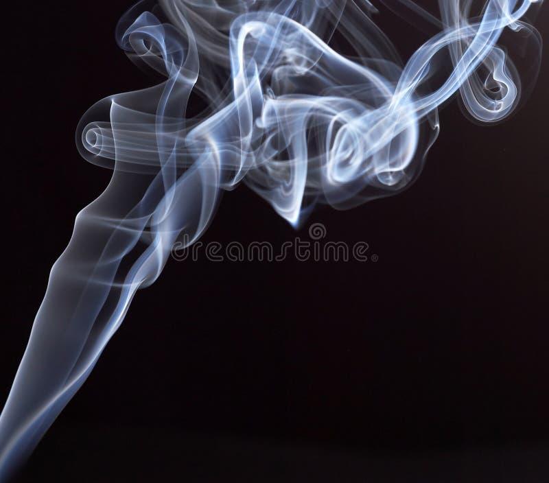 Weißer abstrakter Rauch von den aromatischen Stöcken auf einem schwarzen Hintergrund stockfoto