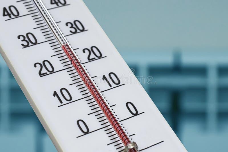 Weißer Alkoholraumthermometer zeigt eine bequeme Temperatur im Haus vor dem hintergrund eines Heizungsheizkörpers lizenzfreie stockfotografie