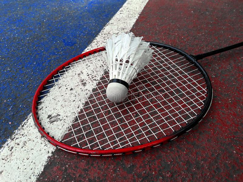 Weißer Badmintonfederball auf Bodenschläger auf den Federballplätzen lizenzfreie stockfotos