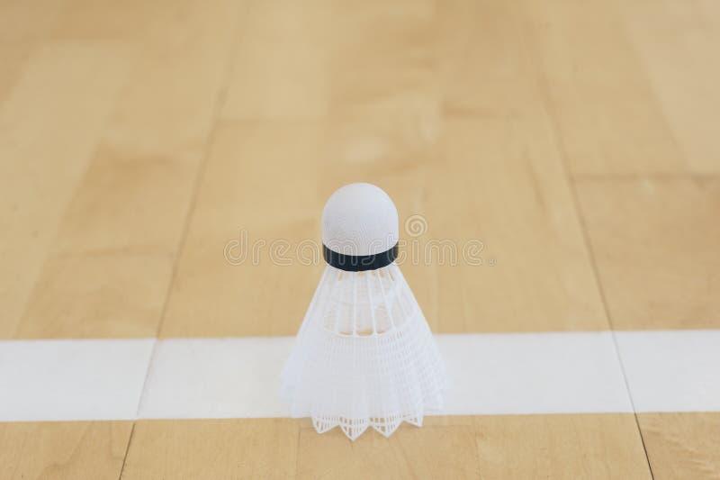 Weißer Badmintonfederball auf einer Linie Hallenboden an den Federballplätzen lizenzfreie stockfotos