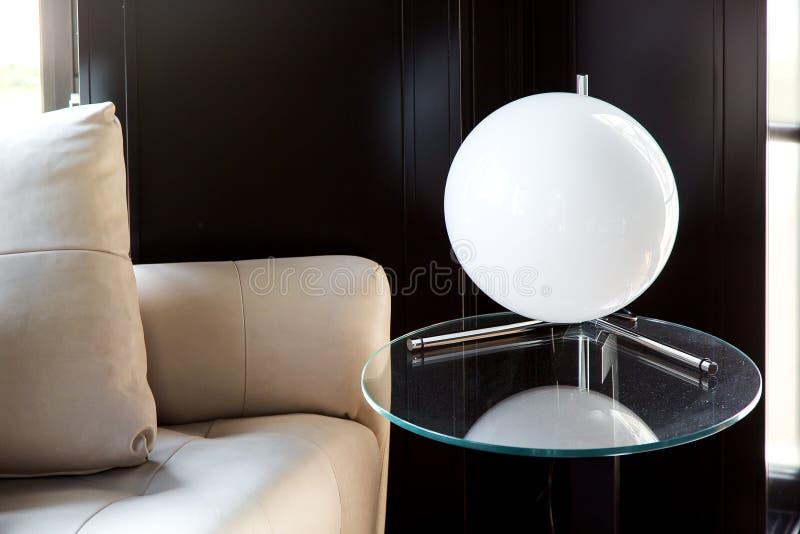 Weißer Ball der Tischlampe auf einem Glasrundtisch stockbild