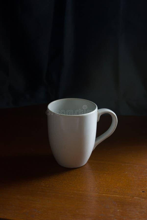 Weißer Becher auf Holztisch mit dunkelblauem Vorhang im Hintergrund, Gefühlentspannung, am besten für Modell stockfotografie