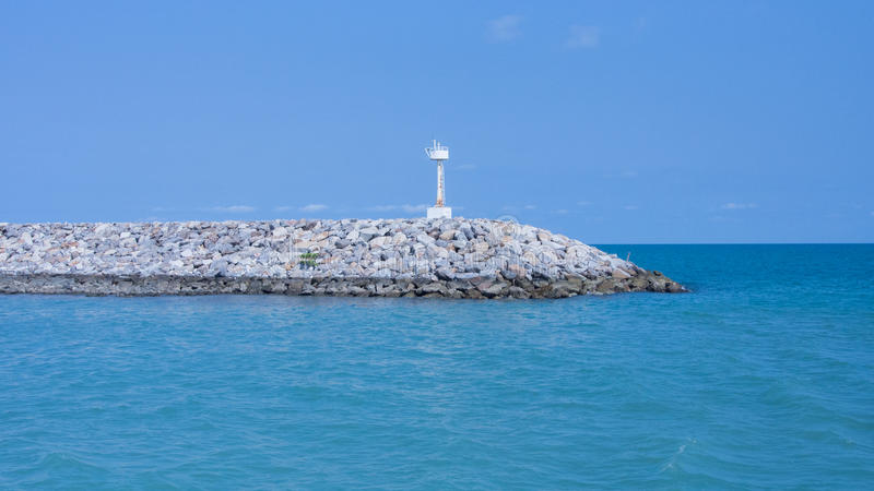 Weißer Beobachter auf dem Felsenpier im blauen Ozean lizenzfreie stockfotografie
