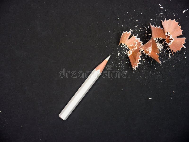 Weißer Bleistift mit dem Schärfen des Abfalls auf schwarzem Hintergrund stockbilder