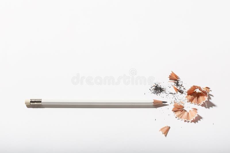 Weißer Bleistift mit dem Schärfen von Schnitzeln auf weißem Hintergrund Zurück zu Schule oder Arbeitskonzept stockbild