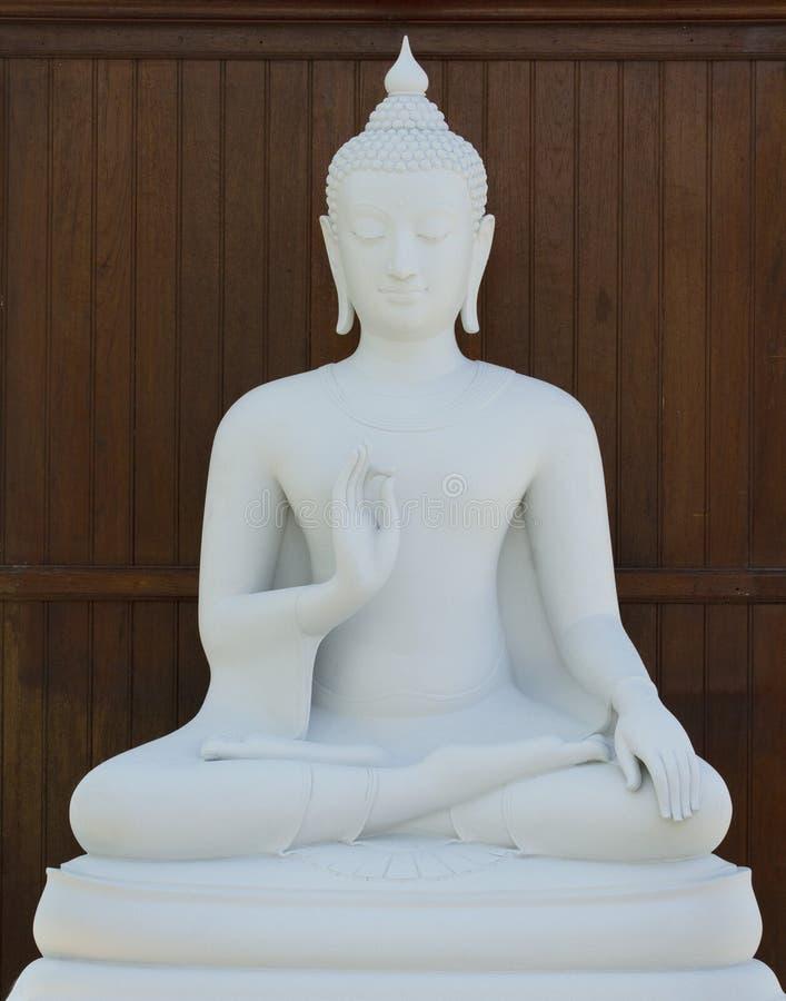 Weißer Buddha auf hölzernem Hintergrund stockfotografie